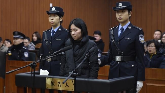 Ladeada de policiais, Mo Huanjing ouve o veredito no tribunal