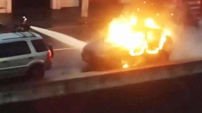 Bombeiro tenta apagar as chamas que destru�ram o ve�culo
