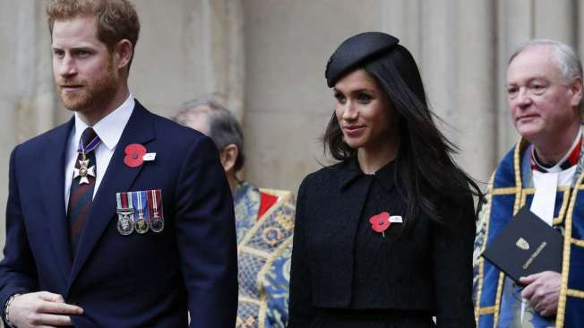 Britain's Prince Harry (L) and his fiancee US actress Meghan Markle (R) walk with each as they leave after attending a service of commemoration and thanksgiving to mark Anzac Day in Westminster Abbey in London on April 25, 2018. Anzac Day marks the anniversary of the first major military action fought by Australian and New Zealand forces during the First World War. The Australian and New Zealand Army Corps (ANZAC) landed at Gallipoli in Turkey during World War I. / AFP PHOTO / Adrian DENNIS