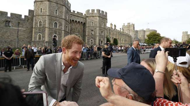 Britain's Prince Harry (L) and his best man Prince William, Duke of Cambridge, greet well-wishers on the street outside Windsor Castle in Windsor on May 18, 2018, the eve of Prince Harry's royal wedding to US actress Meghan Markle.  Britain's Prince Harry and US actress Meghan Markle will marry on May 19 at St George's Chapel in Windsor Castle. / AFP PHOTO / Adrian DENNIS