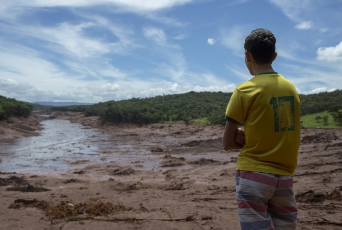 Menino observa área de Casa Grande, afetada pelo desastre da Vale, em Brumadinho