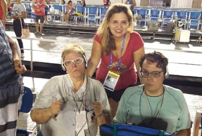 Ana Lúcia Motta, proprietária da All Dubbing, posa com mãe e filho cegos que acompanham o desfile na Sapucaí através do serviço oferecido pela empresa