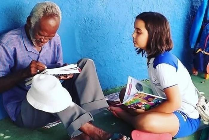 Zezinho escreve, observado de perto por Bárbara