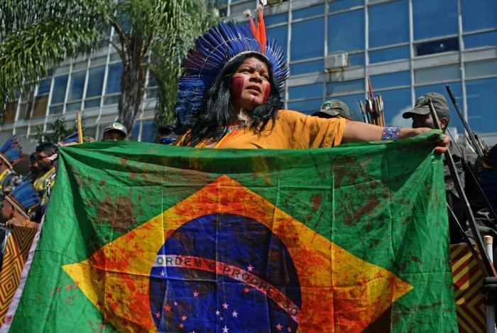 An indigenous woman holds a Brazilian national flags stained in red -as blood- during a march in Brasilia on April 26, 2019, on the last day of a protest to defend indigenous land and rights. - Thousands of indigenous people from different tribes are taking part in protests during the Indigenous National Mobilization (MNI) week, a mobilization which seeks to tackle territorial rights' negotiations with the government. (Photo by CARL DE SOUZA / AFP)