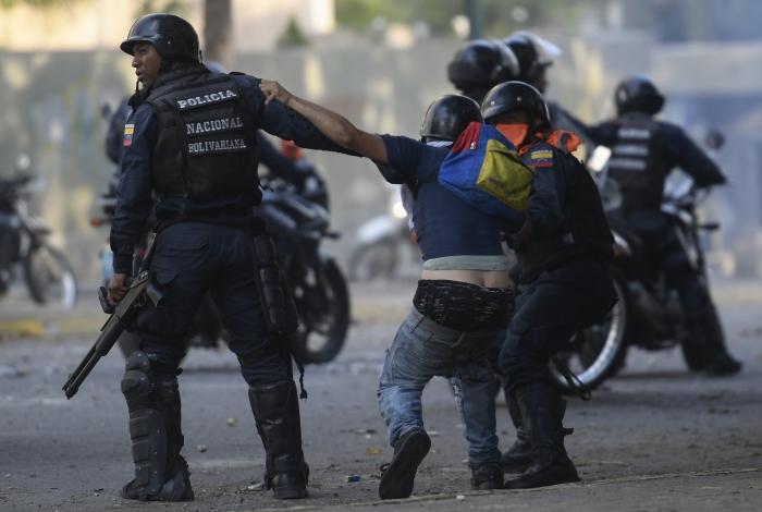 Um manifestante contra o governo é detido pelas forças de segurança durante confrontos com as forças de segurança em Caracas