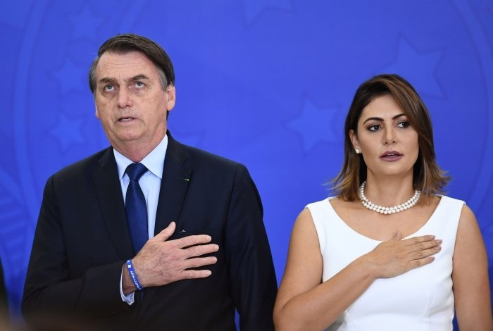 Brazilian President Jair Bolsonaro (L) and first lady Michelle sing the national anthem during the new general officers' promotion ceremony at the Planalto Palace in Brasilia, on April 5, 2019. - Bolsonaro completes his first 100 days of government next April 10. (Photo by EVARISTO SA / AFP)       Caption