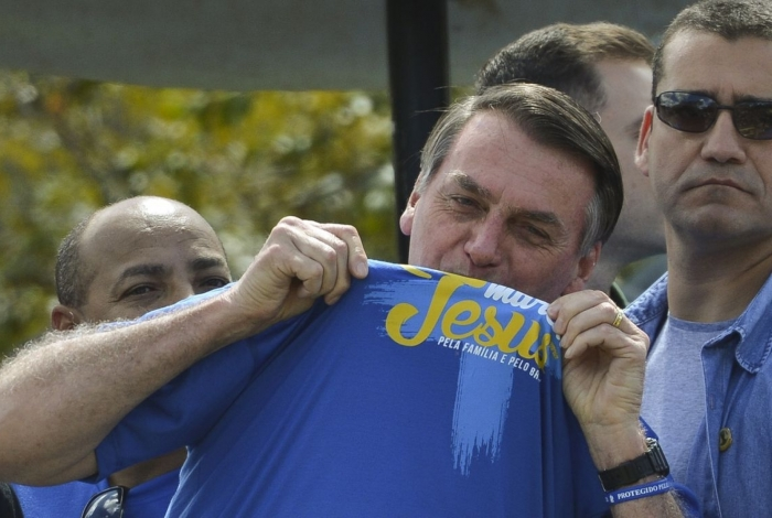O presidente Jair Bolsonaro beija a camisa da Marcha para Jesus, em Brasília