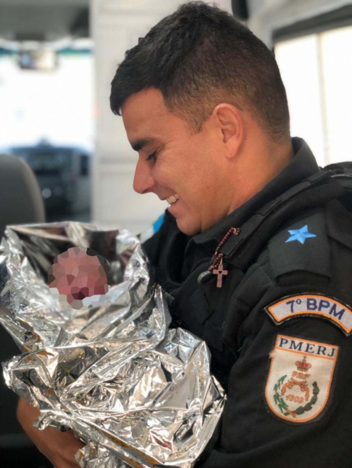 Protegido por manta térmica, bebê é amparado por policial militar