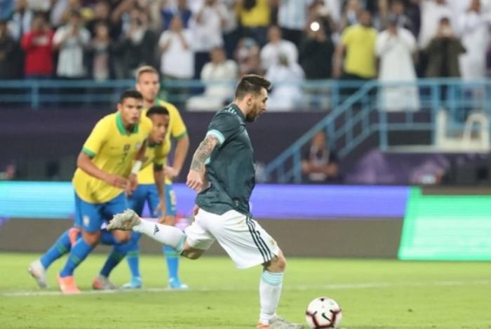 O craque Lionel Messi cobra o pênalti, que foi defendido por Alisson, mas o camisa 10 marcou no rebote