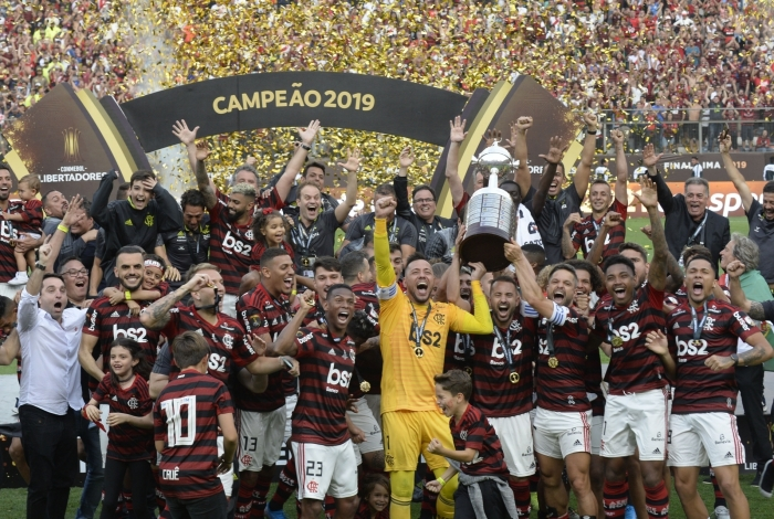 Players of Brazil's Flamengo celebrate on the podium with the trophy after winning the Copa Libertadores final football match by defeating Argentina's River Plate, at the Monumental stadium in Lima, on November 23, 2019. (Photo by Ernesto BENAVIDES / AFP)