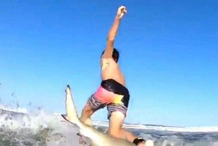 Nas imagens é possível ver o momento em que o garoto está surfando e acaba sendo atingido pelo tubarão