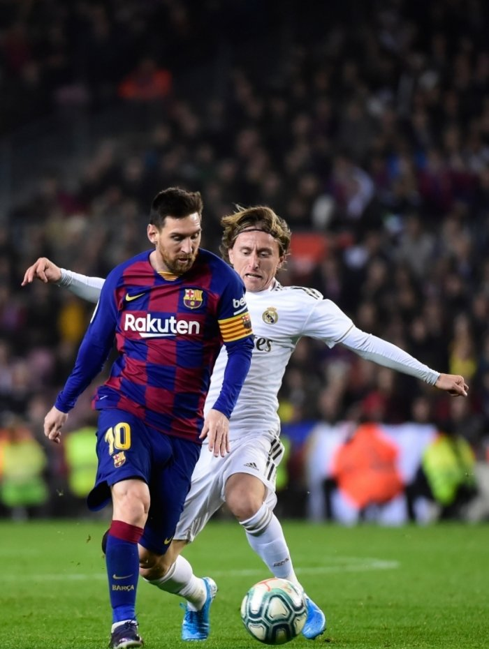Barcelona's Argentine forward Lionel Messi vies with Real Madrid's Croatian midfielder Luka Modric during the