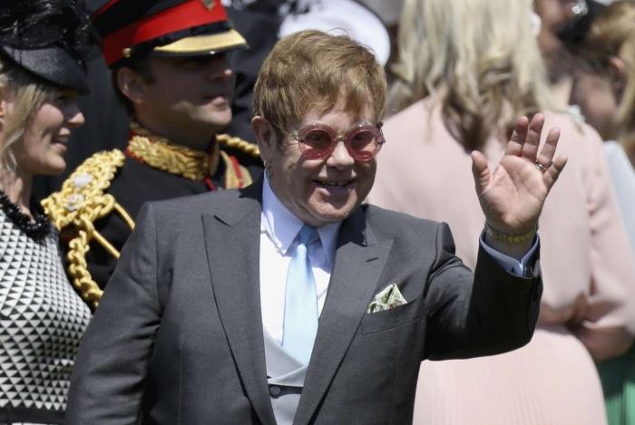 O cantor e compositor britânico Elton John acena ao sair depois de participar da cerimônia de casamento do príncipe Harry, duque de Sussex e da atriz norte-americana Meghan Markle