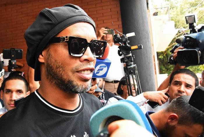 Ronaldinho é cercado por jornalistas ao deixar o prédio do MP