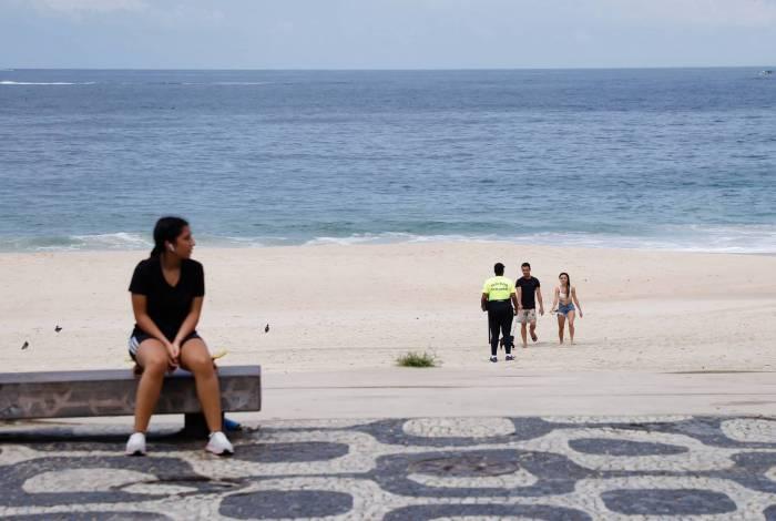 Clima tempo. Movimentacao reduzida em praias da Zona Sul, na manha deste domingo (22). Policial militar orienta pessoas para que saiam da areia da praia, em Ipanema.