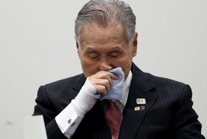 O presidente do comitê organizador, Yoshiro Mori, limpa o nariz na entrevista que confirmou o adiamento