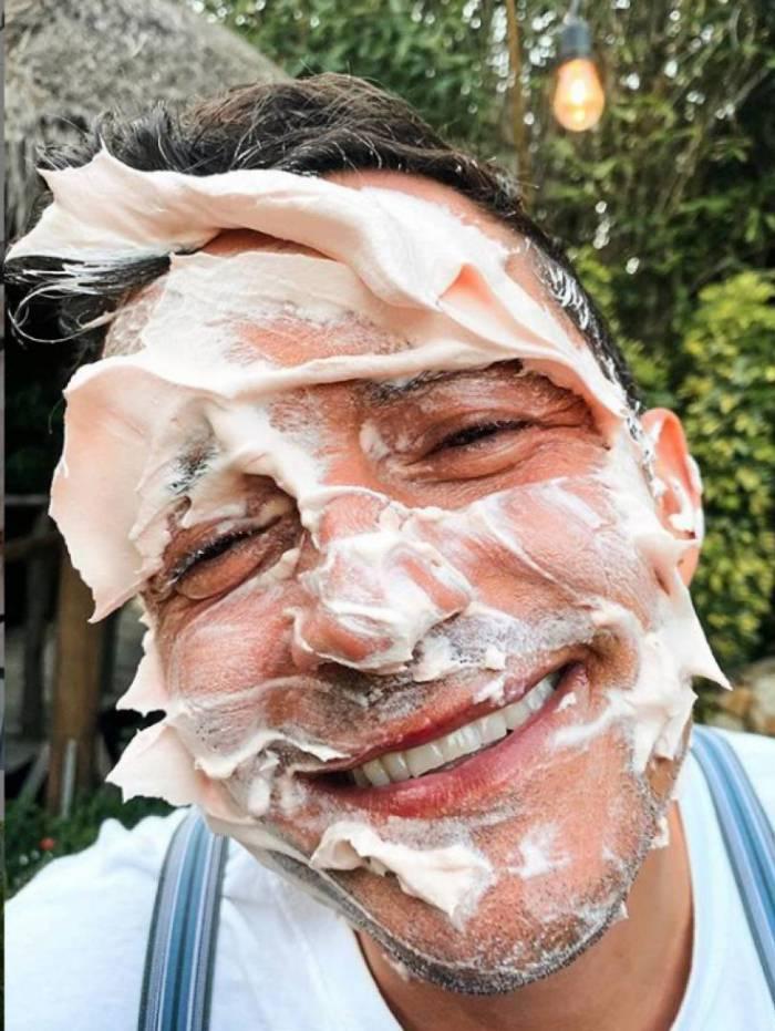 Orlando Bloom com o rosto cheio de creme rosa