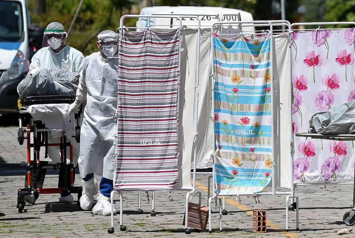 Cadáver de uma vítima do coronavírus é transportado por equipes médicas com roupas de proteção para uma área refrigerada do Hospital João Lucio em Manaus, Amazonas, Brasil