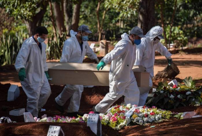 Funcionários do cemitério da Vila Formosa, em São Paulo, realizam o enterro de mais uma vítima do coronavírus