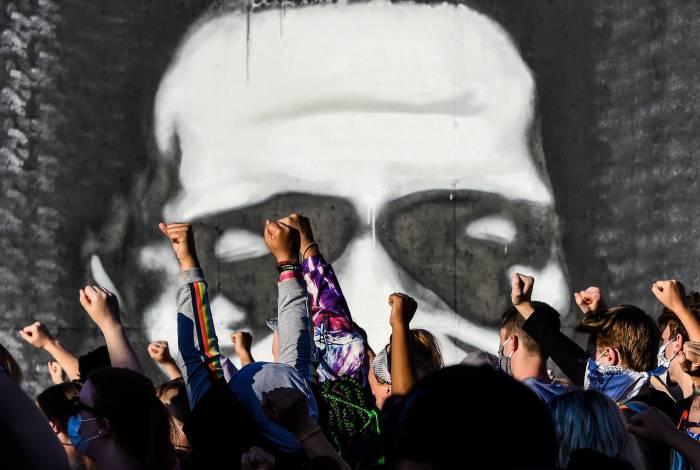 As pessoas levantam as mãos enquanto protestam no memorial improvisado em homenagem a George Floyd, em 4 de junho de 2020 em Minneapolis, Minnesota