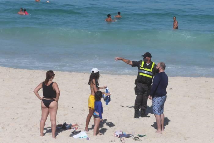 Policial tentar convencer as pessoas a saírem da praia
