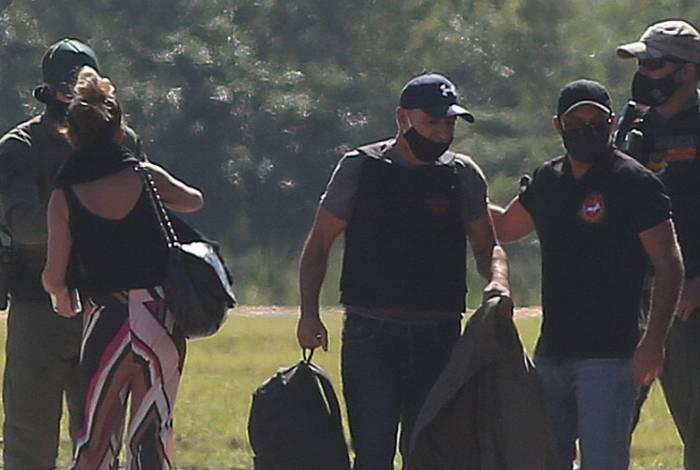 Fabrício Queiroz (E) desembarca no aeroporto de Jacarepaguá, de colete e escoltado por policiais