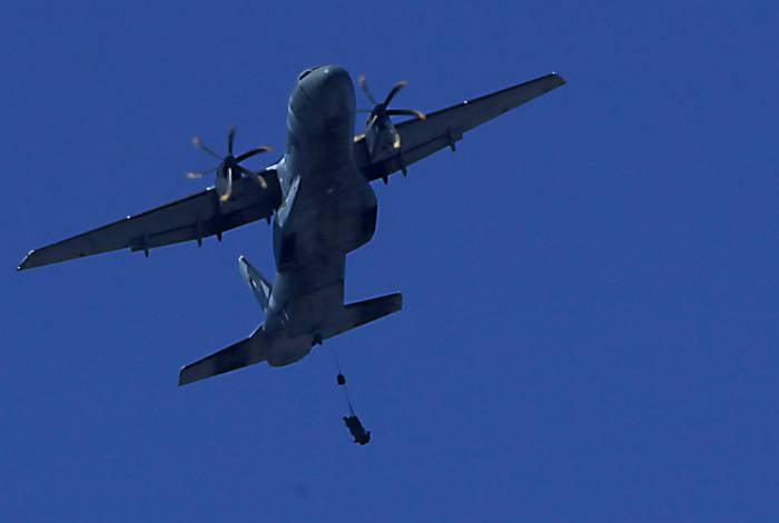 Aeronave sobrevoa Campo dos Afonsos com paraquedista pendurado