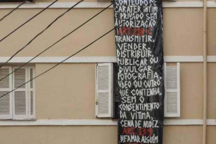 Mulher é fotografada nua pelos vizinhos e pendura faixa de protesto na janela