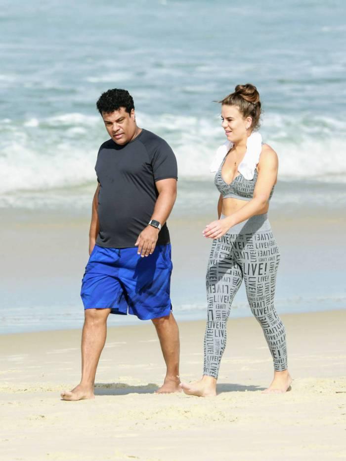 Assis caminha na praia com a mulher