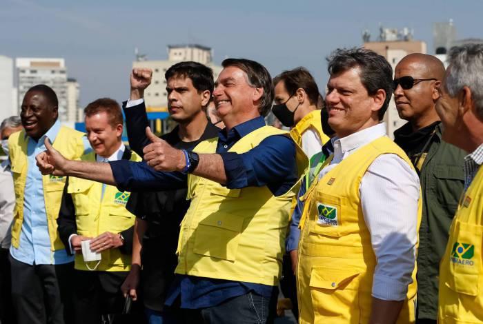 O presidente da República Jair Bolsonaro, posa para foto com operários que participaram das obras de recuperaçãor da pista principal do Aeroporto de Congonhas. .