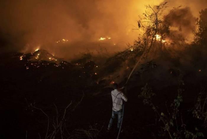 Voluntário tenta conter fogo que chega a uma das pontes que compõem a Transpantaneira, no estado do Mato Grosso