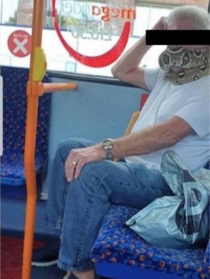Homem usa cobra para cobrir boca e nariz
