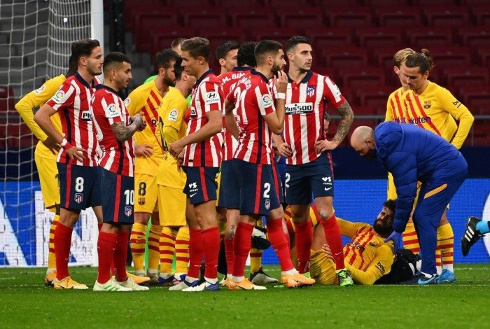 Players gather as Barcelona's Spanish defender Gerard Pique (bottom) receives medical attention during the Spanish League football match between Club Atletico de Madrid and FC Barcelona at the Wanda Metropolitano stadium in Madrid on November 21, 2020. (Photo by GABRIEL BOUYS / AFP)