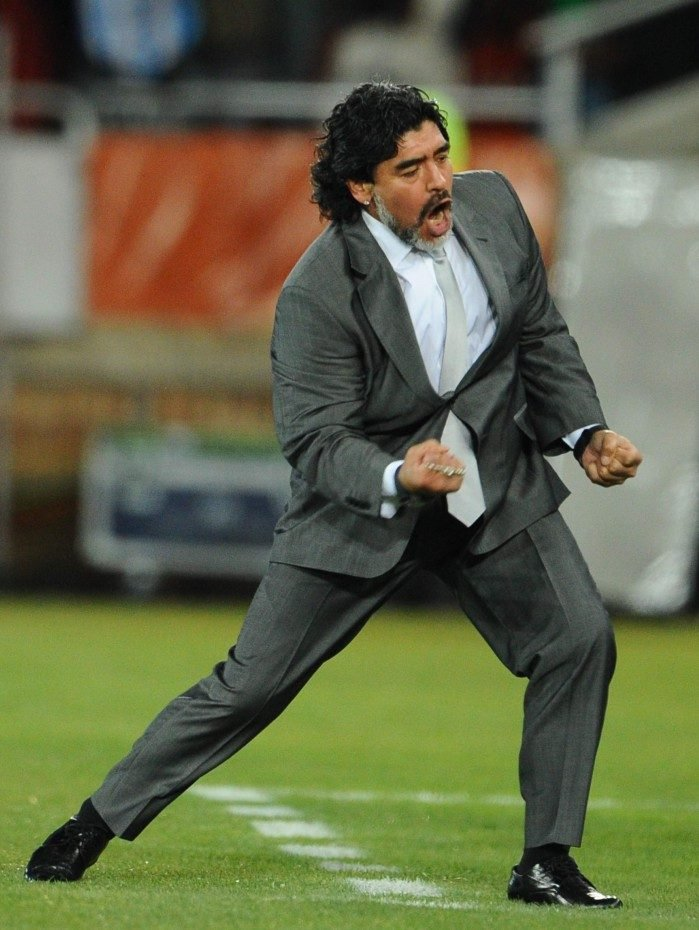 (FILES) In this file photo taken on June 22, 2010 Argentina's coach Diego Maradona celebrates after Argentina's defender Martin Demichelis (not pictured) scored during the Group B first round 2010 World Cup football match Greece vs Argentina at Peter Mokaba stadium in Polokwane. - Argentine football legend Diego Maradona has died at the age of 60, his spokesman announced on November 25, 2020.
