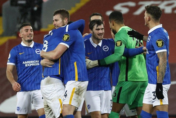 Brighton players celebrate with Brighton's Spanish goalkeeper Robert Sanchez after the English Premier League football match between Liverpool and Brighton and Hove Albion at Anfield in Liverpool, north west England on February 3, 2021. Brighton won the match 1-0. PHIL NOBLE / POOL / AFP