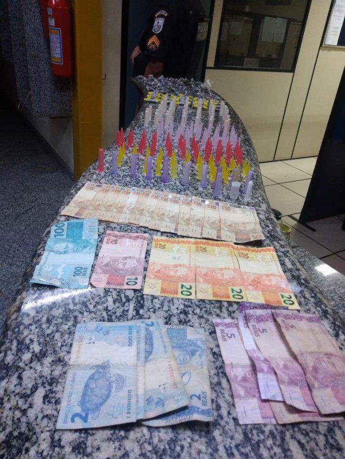 Foram apreendidas 80 buchas de maconha, 57 pinos de cocaína, 128 pinos vazios, R$ 833 e o veículo.