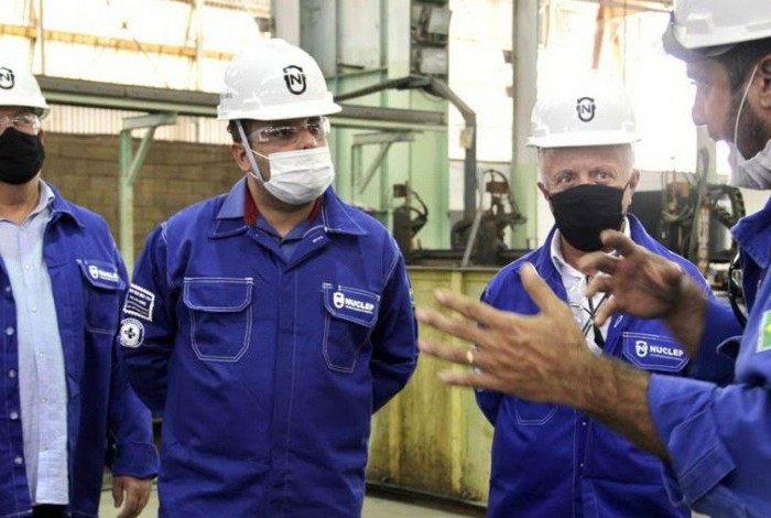 Valter Almeida (de óculos transparente) com Carlos Seixas, presidente da Nuclep, escuta atentamente explicação de um funcionário no pátio da fábrica