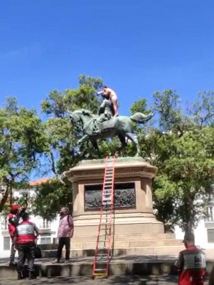Nu, homem sobe em estátua e se nega a descer até ser vacinado