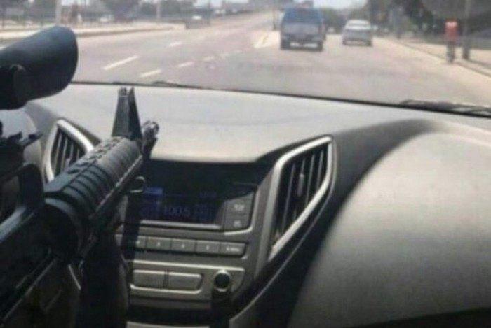 De dentro do carro, criminoso mostra fuzil e circula atrás de uma viatura da PM