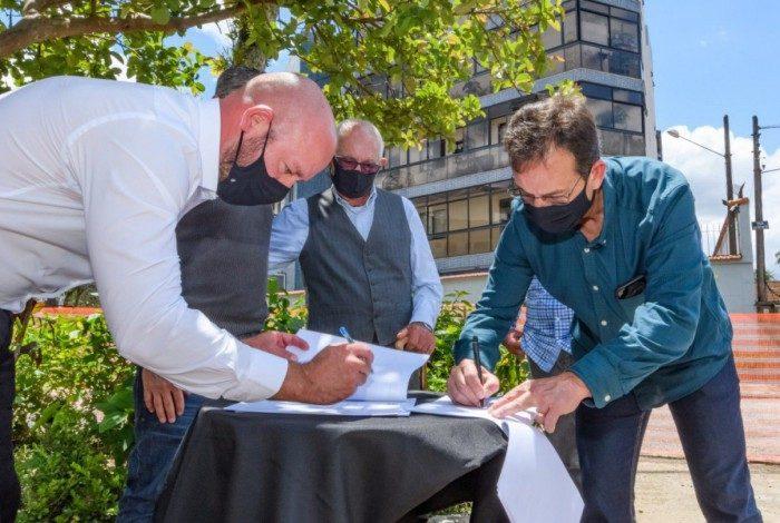 Prefeito Vinicius Claussen e o empresário Raul Machado Alves Filho na assinatura do termo de adoção