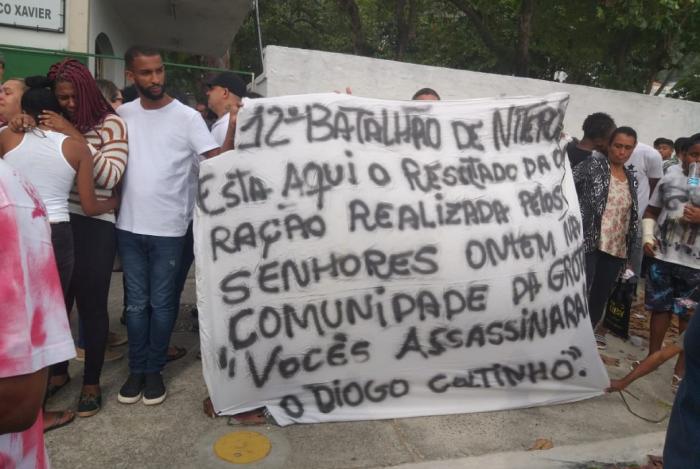 Moradores exibem cartaz de protesto cobrando planejamento em operações policiais na favela durante enterro de adolescente morto na Comunidade da Grota, em Niterói